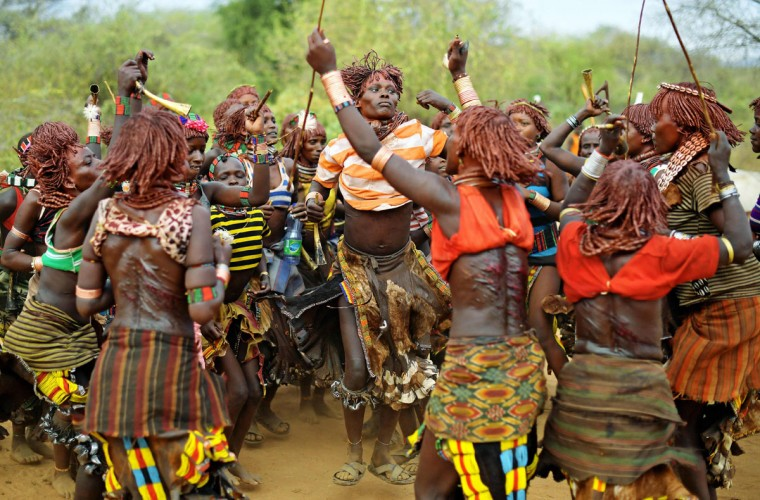 """Hamar women dance before a bull jumping ceremony in Ethiopia's southern Omo Valley region near Turmi on September 19, 2016. The Hamar are a Nilotic ethnic group in Ethiopia. The construction of the Gibe III dam, the third largest hydroelectric plant in Africa, and large areas of very """"thirsty"""" cotton and sugar plantations and factories along the Omo river are impacting heavily on the lives of tribes living in the Omo Valley who depend on the river for their survival and way of life. Human rights groups fear for the future of the tribes if they are forced to scatter, give up traditional ways through loss of land or ability to keep cattle as globalisation and development increases. (AFP PHOTO / CARL DE SOUZA)"""