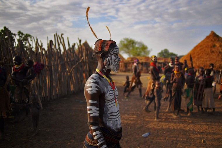 """Members of the Karo tribe pose in Ethiopia's southern Omo Valley region on September 23, 2016. The Karo are a Nilotic ethnic group in Ethiopia famous for their body painting. They are also one of the smallest tribes in the region. The construction of the Gibe III dam, the third largest hydroelectric plant in Africa, and large areas of very """"thirsty"""" cotton and sugar plantations and factories along the Omo river are impacting heavily on the lives of tribes living in the Omo Valley who depend on the river for their survival and way of life. Human rights groups fear for the future of the tribes if they are forced to scatter, give up traditional ways through loss of land or ability to keep cattle as globalisation and development increases. (AFP PHOTO / CARL DE SOUZA)"""