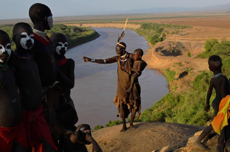 """Members of the Karo tribe pose in front of the Omo river in Ethiopia's southern Omo Valley region on September 23, 2016. The Karo are a Nilotic ethnic group in Ethiopia famous for their body painting. They are also one of the smallest tribes in the region. The construction of the Gibe III dam, the third largest hydroelectric plant in Africa, and large areas of very """"thirsty"""" cotton and sugar plantations and factories along the Omo river are impacting heavily on the lives of tribes living in the Omo Valley who depend on the river for their survival and way of life. Human rights groups fear for the future of the tribes if they are forced to scatter, give up traditional ways through loss of land or ability to keep cattle as globalisation and development increases. (AFP PHOTO / CARL DE SOUZA)"""