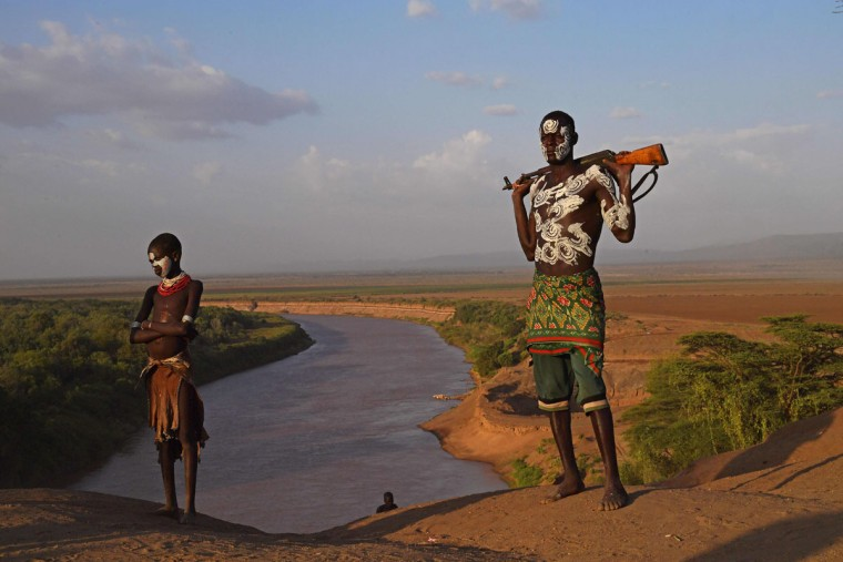 """Members from the Karo tribe pose in front of the Omo river in Ethiopia's southern Omo Valley region on September 23, 2016. The Karo are a Nilotic ethnic group in Ethiopia famous for their body painting. They are also one of the smallest tribes in the region. The construction of the Gibe III dam, the third largest hydroelectric plant in Africa, and large areas of very """"thirsty"""" cotton and sugar plantations and factories along the Omo river are impacting heavily on the lives of tribes living in the Omo Valley who depend on the river for their survival and way of life. Human rights groups fear for the future of the tribes if they are forced to scatter, give up traditional ways through loss of land or ability to keep cattle as globalisation and development increases. (AFP PHOTO / CARL DE SOUZA)"""