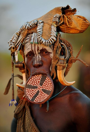 """A woman from the Mursi tribe poses for a photo in the Mago National park near Jinka in Ethiopia's southern Omo Valley region on September 21, 2016. The Mursi are a Nilotic pastoralist ethnic group which number around 10,000 people in Ethiopia. Some Mursi women choose to wear a saucer lip plate (dhebi a tugoin). A girls lower lip is cut when she reaches the age of 15 or 16. The wound is then stretched over time to accomodate a large clay plate. The Mursi tribe are one of the few tribes left who continue this practise. The construction of a sugar factory in Mago National Park has begun to change the way of life for many Mursi as they begin to leave their traditional way of life to work at the factory. Human rights groups also report that the Mursi fear eviction by the Ethiopian government from a large area of the park altogether. The construction of the Gibe III dam, the third largest hydroelectric plant in Africa, and large areas of very """"thirsty"""" cotton and sugar plantations and factories along the Omo river are impacting heavily on the lives of tribes living in the Omo Valley who depend on the river for their survival and way of life. Human rights groups fear for the future of the tribes if they are forced to scatter, give up traditional ways through loss of land or ability to keep cattle as globalisation and development increases. (AFP PHOTO / CARL DE SOUZA)"""