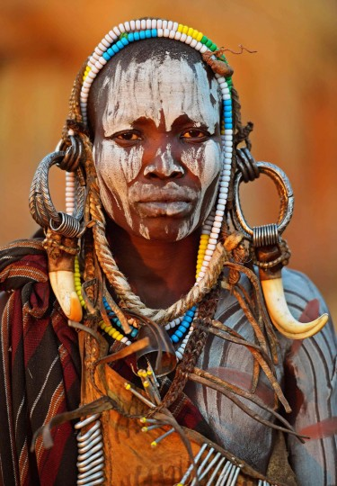 """A woman from the Mursi tribe poses for a photo in the Mago National park near Jinka in Ethiopia's southern Omo Valley region on September 21, 2016. The Mursi are a Nilotic pastoralist ethnic group which number around 10,000 people in Ethiopia. Some Mursi women choose to wear a saucer lip plate (dhebi a tugoin). A girls lower lip is cut when she reaches the age of 15 or 16. The wound is then stretched over time to accomodate a large clay plate. The Mursi tribe are one of the few tribes left who continue this practise. The construction of a sugar factory in Mago National Park has begun to change the way of life for many Mursi as they begin to leave their traditional way of life to work at the factory. Human rights groups also report that the Mursi fear eviction by the Ethiopian government from a large area of the park altogether. The construction of the Gibe III dam, the third largest hydroelectric plant in Africa, and large areas of very """"thirsty"""" cotton and sugar plantations and factories along the Omo river are impacting heavily on the lives of tribes living in the Omo Valley who depend on the river for their survival and way of life. Human rights groups fear for the future of the tribes if they are forced to scatter, give up traditional ways through loss of land or ability to keep cattle as globalisation and development increases. / (AFP PHOTO / CARL DE SOUZA)"""