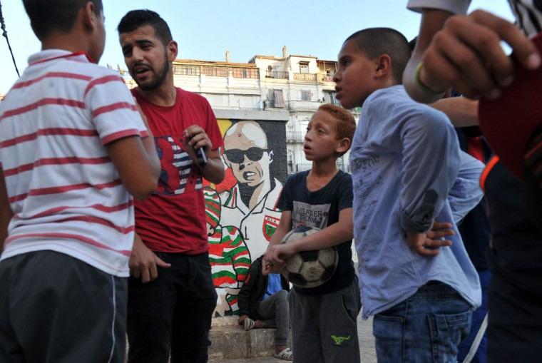 Algerians talk about football in the street in the Bab el-Oued neighborhood, which is historically known to be predominantly supporting Mouloudia Club Alger (MCA) football team in Algiers on October 11, 2016, two days ahead of the 100th derby match against their rival Union Sportive Medina d'Alger (USMA). (AFP PHOTO / Ryad Kramdi)