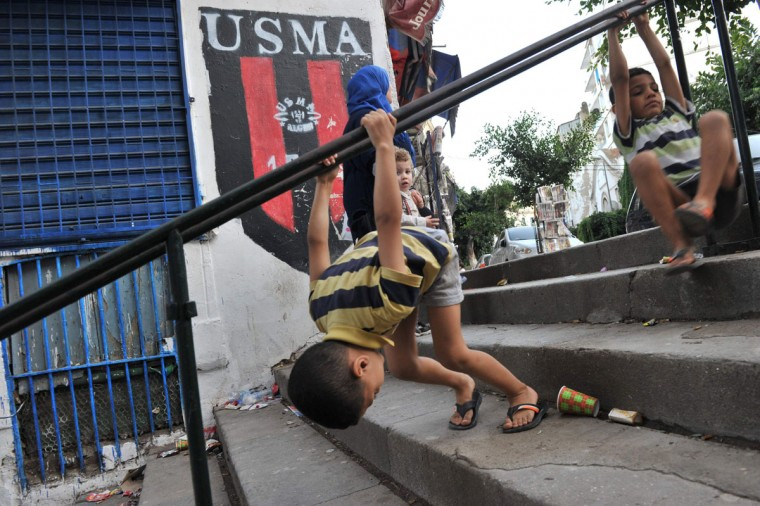 "Algerian children play in front of a shop bearing the colors of the Union Sportive Medina d'Alger (USMA) football club in the Soustara neighborhood, in the old part of Algiers known as the ""Casbah"", which is historically known to be predominantly supporting USMA, on October 11, 2016, two days ahead of the 100th derby match against their rival Mouloudia Club d'Alger (MCA). (AFP PHOTO / Ryad Kramdi)"