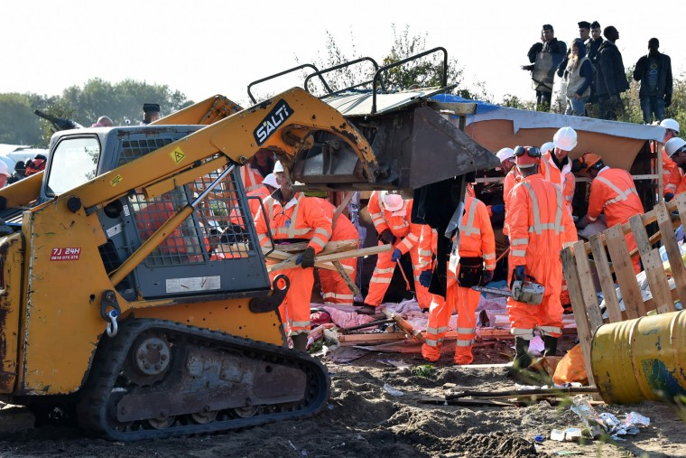 "Workers begin the demolition of the Calais ""Jungle"" camp, in Calais, northern France, on October 25, 2016 as hundreds of migrants boarded buses on the second day of a massive operation to clear the squalid settlement. More than 1,900 left the slum on October 24, ahead of work to tear down the makeshift shelters and eateries in the camp that has become a symbol of Europe's refugee crisis. (Philippe Huguen/AFP/Getty Images)"