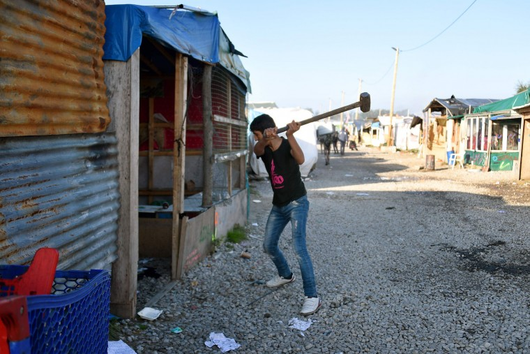 "A migrant takes part in the demolition of the Calais ""Jungle"" camp, in Calais, northern France, on October 25, 2016. Workers escorted by scores of French police officers moved into the ""Jungle"" in Calais on October 25, demolishing shacks and tents emptied of migrants being bussed to shelters around France. The workers used electric saws to take down wooden shelters and earth-moving equipment to carry debris away from the sprawling camp that people have used for years as a launchpad for attempts to reach Britain. (Denis Charlet/AFP/Getty Images)"