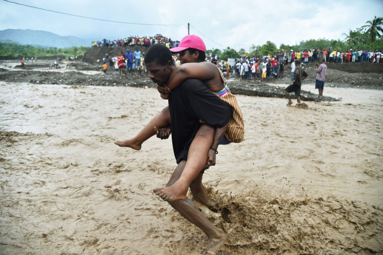 A man carries a woman across a river at Petit Goave where a bridge collapsed during the rains of the Hurricane Matthew, southwest of Port-au-Prince, October 5, 2016. Haiti and the eastern tip of Cuba -- blasted by Matthew on October 4, 2016 -- began the messy and probably grim task of assessing the storm's toll. Matthew hit them as a Category Four hurricane but has since been downgraded to three, on a scale of five, by the US National Hurricane Center. (Hector Retamal/AFP/Getty Images)