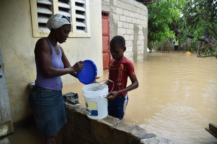 Jonnathan carries water for his mother who is cleaning up her flooded home following the overflowing of La Rouyonne river in the commune of Leogane, south of Port-au-Prince, October 5, 2016. Haiti and the eastern tip of Cuba -- blasted by Matthew on October 4, 2016 -- began the messy and probably grim task of assessing the storm's toll. Matthew hit them as a Category Four hurricane but has since been downgraded to three, on a scale of five, by the US National Hurricane Center. (Hector Retamal/AFP/Getty Images)