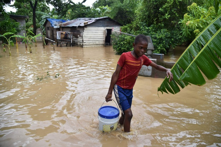 Jonnathan fetches clean water for his mother cleaning his home flooded by the overflowing of the La Rouyonne river in the commune of Leogane, south of Port-au-Prince, October 5, 2016. Haiti and the eastern tip of Cuba -- blasted by Matthew on October 4, 2016 -- began the messy and probably grim task of assessing the storm's toll. Matthew hit them as a Category Four hurricane but has since been downgraded to three, on a scale of five, by the US National Hurricane Center. (Hector Retamal/AFP/Getty Images)