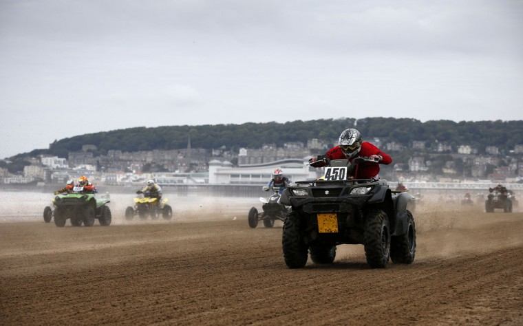 Riders race down the beach during the Adult Quad and Sidecar race during the 2016 HydroGarden Weston Beach Race in Weston-super-Mare, south west England, on October 8, 2016. Beach racing is an offshoot of enduro and motocross racing. Riders on solo motorcycles and quad bikes compete on a course marked out on a beach, with man-made jumps and sand dunes being constructed to make the course tougher. (ADRIAN DENNIS/AFP/Getty Images)