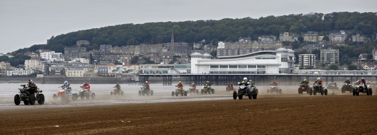 Riders race down the beach during the Adult Quad and Sidecar race at the 2016 HydroGarden Weston Beach Race in Weston-super-Mare, south west England, on October 8, 2016. Beach racing is an offshoot of enduro and motocross racing. Riders on solo motorcycles and quad bikes compete on a course marked out on a beach, with man-made jumps and sand dunes being constructed to make the course tougher. (ADRIAN DENNIS/AFP/Getty Images)