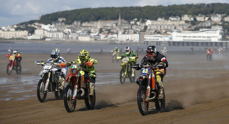 Riders race down the beach during the Adult Solo race at the HydroGarden Weston Beach Race in Weston-super-Mare, south west England, on October 9, 2016. Beach racing is an offshoot of enduro and motocross racing. Riders on solo motorcycles and quad bikes compete on a course marked out on a beach, with man-made jumps and sand dunes being constructed to make the course tougher. (ADRIAN DENNIS/AFP/Getty Images)