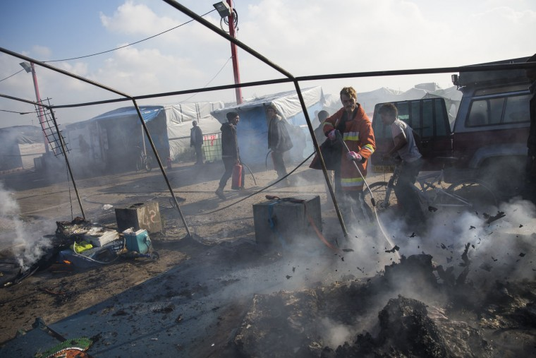 A firefighter sprays water on the remains of a migrants' tent after it was set alight at the Jungle migrant camp on October 25, 2016 in Calais, France. Many migrants have left by coach to be relocated at centres across France as Police and officials in France begin to clear the 'Jungle' migrant camp in Calais. Some 7,000 people are estimated to be living in the camp in squalid conditions. (Photo by Jack Taylor/Getty Images)