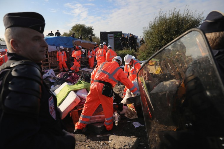 French police stand guard at the notorious 'Jungle' camp as authorities begin to demolish the site on October 25, 2016 in Calais, France. Many migrants have left by coach to be reloctated at centres across France as Police and officials in France begin to clear the 'Jungle' migrant camp in Calais. Some 7,000 people are estimated to be living in the camp in squalid conditions. (Photo by Christopher Furlong/Getty Images)