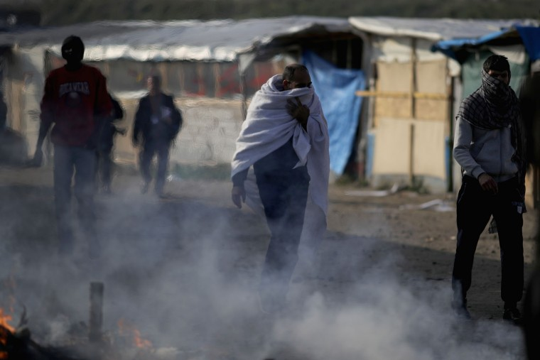 Migrants walk past burning tents at the notorious Jungle camp as authorities begin demolish the site on October 25, 2016 in Calais, France. Many migrants have left by coach to be relocated at centres across France as Police and officials in France begin to clear the 'Jungle' migrant camp in Calais. Some 7,000 people are estimated to be living in the camp in squalid conditions. (Photo by Christopher Furlong/Getty Images)