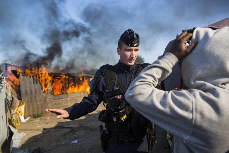 A police officer stands guard after migrants burn down a shelter as authorities move in to clear the Jungle migrant camp on October 25, 2016 in Calais, France. Migrants are leaving the Jungle migrant and refugee camp by coach for a second day as French authorities clear the camp of an estimated 7000 people ahead of its demolition. (Photo by Jack Taylor/Getty Images)