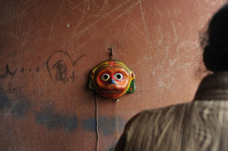 A mask hangs on a wall as a Nepalese Hindu devotee dresses as a deity in preparation for celebration of the Shikali Jatra festival at the Shikali Temple in the village of Khokana, on the outskirts of Kathmandu on October 7, 2016. Local villagers, who normally do not celebrate the country's most famous festival of Dashain, celebrate the Shikali Jatra each year. (Prakash Mathema/AFP/Getty Images)
