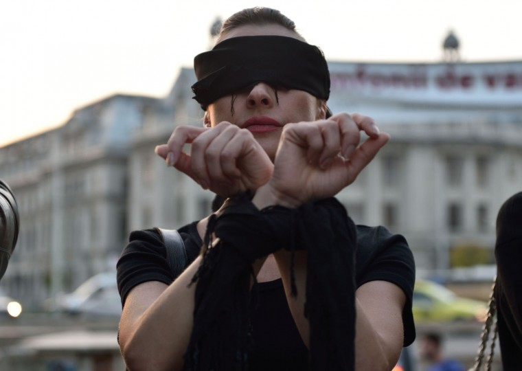 "A Romanian woman shows support with Polish women on strike during a flashmob in Piata Universitatii square in Bucharest on October 3, 2016. Thousands of women dressed in black protested across Poland in the ""Women strike"" campaign against a proposed near-total abortion ban in the devoutly Catholic country where legislation is already among the most restrictive in Europe. (Daniel Mihailescu/AFP/Getty Images)"