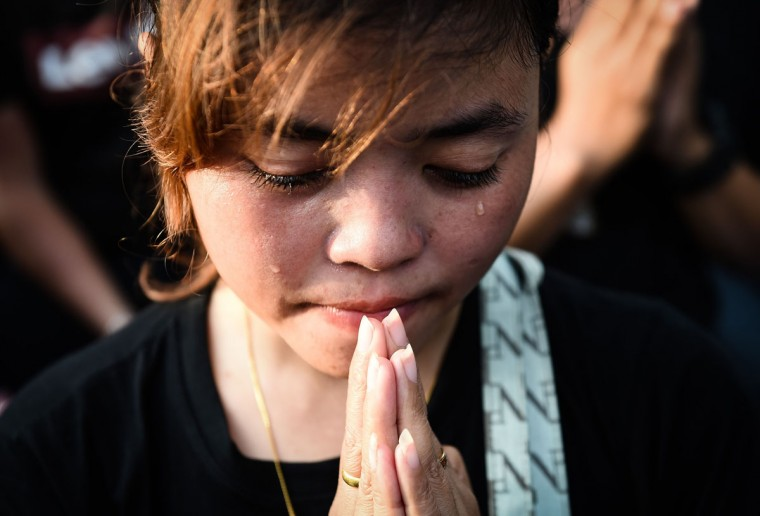 A woman cries as the hearse carrying the body of the late Thai King Bhumibol Adulyadej passes the Grand Palace in Bangkok on October 14, 2016. Bhumibol, the world's longest-reigning monarch, passed away aged 88 on October 13, 2016 after years of ill health, removing a stabilising father figure from a country where political tensions remain two years after a military coup. / (AFP Photo/Lillian Suwanrumpha)