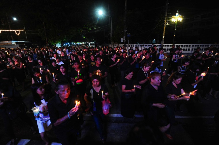 Mourners wearing black hold candles to pay respects to the late Thai King Bhumibol Adulyadej in the southern province of Narathiwat on October 14, 2016. Massive crowds of weeping Thais and saluting soldiers lined the streets Friday as late King Bhumibol Adulyadej was borne through Bangkok, a day after his death left an apprehensive country facing an uncertain future. / (AFP Photo/Madaree Tohlala)