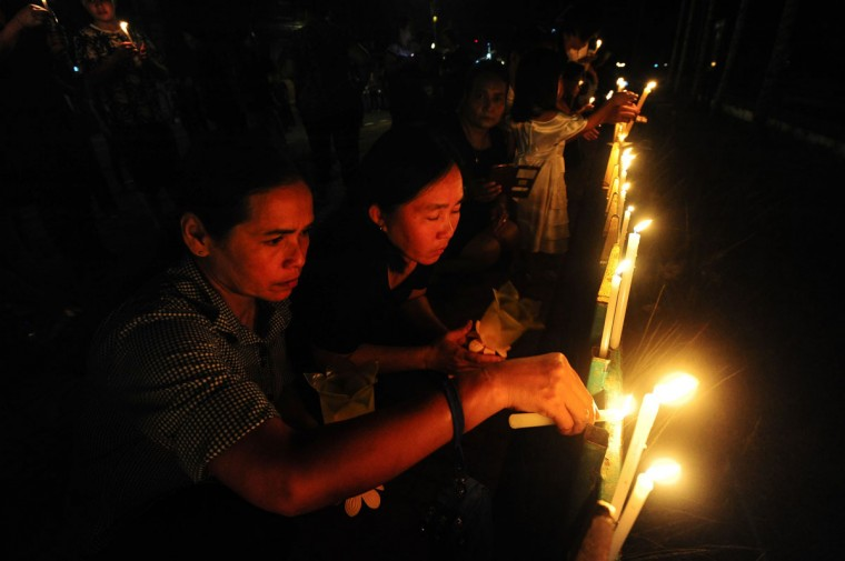 Mourners light candles to pay respects to the late Thai King Bhumibol Adulyadej in the southern province of Narathiwat on October 14, 2016. Massive crowds of weeping Thais and saluting soldiers lined the streets Friday as late King Bhumibol Adulyadej was borne through Bangkok, a day after his death left an apprehensive country facing an uncertain future. / (AFP Photo/Madaree Tohlala)