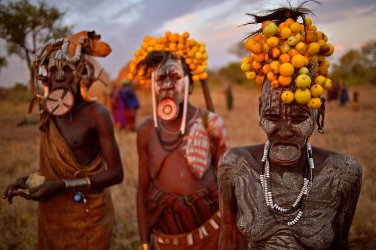 """Women from the Mursi tribe pose for a photo in the Mago National park near Jinka in Ethiopia's southern Omo Valley region on September 21, 2016. The Mursi are a Nilotic pastoralist ethnic group which number around 10,000 people in Ethiopia. Some Mursi women choose to wear a saucer lip plate (dhebi a tugoin). A girls lower lip is cut when she reaches the age of 15 or 16. The wound is then stretched over time to accomodate a large clay plate. The Mursi tribe are one of the few tribes left who continue this practise. The construction of a sugar factory in Mago National Park has begun to change the way of life for many Mursi as they begin to leave their traditional way of life to work at the factory. Human rights groups also report that the Mursi fear eviction by the Ethiopian government from a large area of the park altogether. The construction of the Gibe III dam, the third largest hydroelectric plant in Africa, and large areas of very """"thirsty"""" cotton and sugar plantations and factories along the Omo river are impacting heavily on the lives of tribes living in the Omo Valley who depend on the river for their survival and way of life. Human rights groups fear for the future of the tribes if they are forced to scatter, give up traditional ways through loss of land or ability to keep cattle as globalisation and development increases. / (AFP PHOTO / CARL DE SOUZA)"""