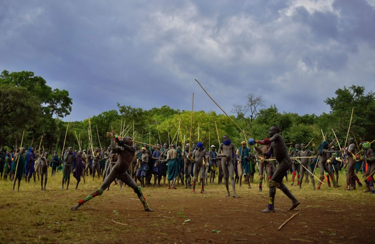 """Men from the Suri tribe take part in a """"Donga"""" or stick fight in Ethiopia's southern Omo Valley region near Kibbish on September 24, 2016. Traditionally the fight is a way to impress women and find a wife. The fights are brutal and sometimes result in death. The combatants fight with little or no clothing and sometimes no protection at all. The Suri are a pastoralist Nilotic ethnic group in Ethiopia. The construction of the Gibe III dam, the third largest hydroelectric plant in Africa, and large areas of very """"thirsty"""" cotton and sugar plantations and factories along the Omo river are impacting heavily on the lives of tribes living in the Omo Valley who depend on the river for their survival and way of life. Human rights groups fear for the future of the tribes if they are forced to scatter, give up traditional ways through loss of land or ability to keep cattle as globalisation and development increases. (AFP PHOTO / CARL DE SOUZA)"""