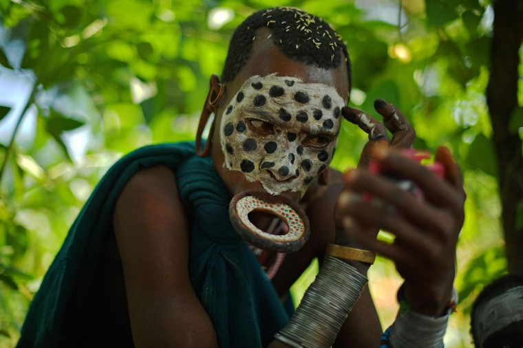 """A woman from the Suri tribe wearing a lip plate paints her face in Ethiopia's southern Omo Valley region near Kibbish on September 25, 2016. The Suri are a pastoralist Nilotic ethnic group in Ethiopia. The construction of the Gibe III dam, the third largest hydroelectric plant in Africa, and large areas of very """"thirsty"""" cotton and sugar plantations and factories along the Omo river are impacting heavily on the lives of tribes living in the Omo Valley who depend on the river for their survival and way of life. Human rights groups fear for the future of the tribes if they are forced to scatter, give up traditional ways through loss of land or ability to keep cattle as globalisation and development increases. (AFP PHOTO / CARL DE SOUZA)"""