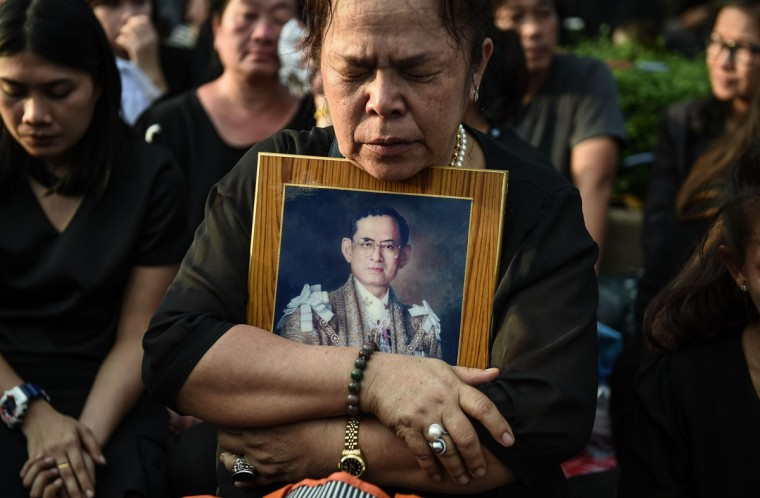 A mourner clutches a picture of Thai King Bhumibol Adulyadej after the hearse carrying the body of the late monarch passes the Grand Palace in Bangkok on October 14, 2016.Bhumibol, the world's longest-reigning monarch, passed away aged 88 on October 13, 2016 after years of ill health, removing a stabilising father figure from a country where political tensions remain two years after a military coup. / (AFP Photo/Lillian Suwanrumpha)