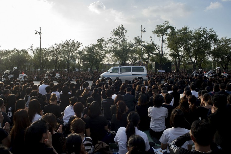A motorcade carries the body of King Bhumibol Adulyadej to the Grand Palace while people kneel to pay respect to him on October 14, 2016 in Bangkok, Thailand. Thailand's King Bhumibol Adulyadej, the world's longest-reigning monarch, died at the age of 88 in Bangkok's Siriraj Hospital on Thursday after his 70-year reign. Prime Minister Prayut Chan-ocha made a statement Thailand would hold a one-year mourning period as the Crown Prince Maha Vajiralongkorn confirmed that he would perform his duty as heir to the throne. (Photo by Borja Sanchez Trillo/Getty Images)