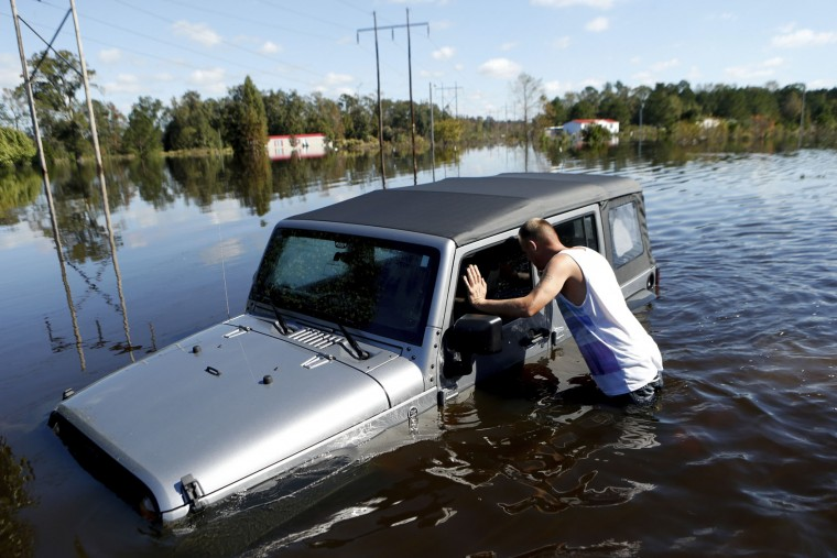 After coming across a Jeep surrounded by floodwaters associated with Hurricane Matthew, Elmer McDonald inspects the interior to make certain nobody was inside as he makes his way through a strong current after checking on his own mobile home for the first time on Thursday, Oct. 13, 2016, in Lumberton, N.C. About 1,200 Lumberton residents had to be evacuated by boat and plucked from their roofs by helicopters as the river crested; McDonald was one of thousands who evacuated. (AP Photo/Brian Blanco)