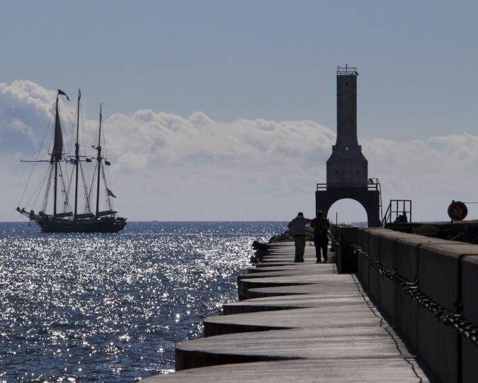 In this photo taken Oct. 3, 2016, the Denis Sullivan ship passes by the light head tower on the Port Washington, Wis. breakwater. About 120 lighthouses no longer critical to the U.S. Coast Guard in 22 states and Puerto Rico have been acquired at no cost by government entities and nonprofits, or sold to private individuals eager to preserve the landmarks and tap into their tourism potential since they became available under the National Historic Lighthouse Preservation Act of 2000. (AP Photo/Carrie Antlfinger)