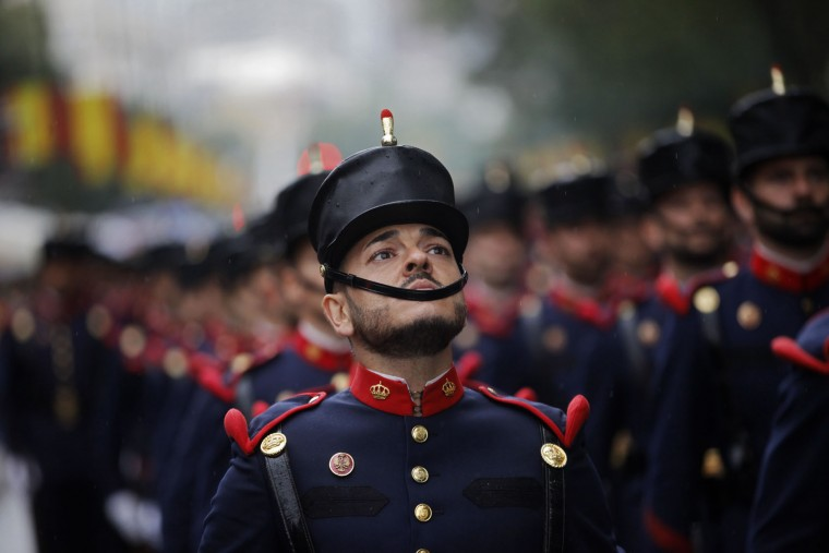 "A Spanish soldier looks up as he marches with others in a military parade during a national holiday known as ""Dia de la Hispanidad"" or Hispanic Day, in Madrid, Spain, Wednesday, Oct. 12, 2016. Almost a year into Spain's political deadlock, the country is celebrating its National Day with a military parade of over 3,000 soldiers marching through Madrid and aircraft drawing trails of red and yellow smoke in the sky to represent the flag. (AP Photo/Francisco Seco)"