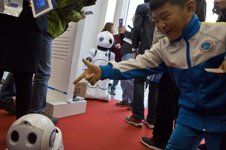 A child pretends to shoot a companion robot during the World Robot Conference in Beijing, China, Friday, Oct. 21, 2016. The conference showcased China's burgeoning robot industry as the nation seeks to increase the use of robots in its manufacturing and service industries. (AP Photo/Ng Han Guan)