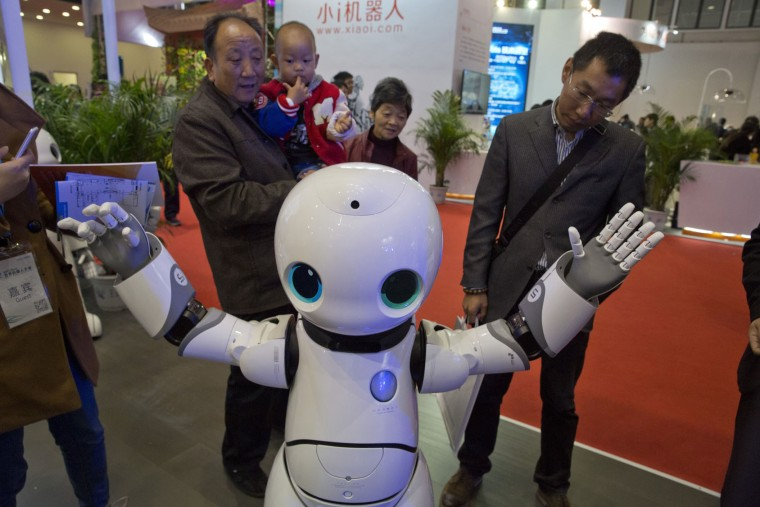 Visitors look at the Canbot companion robot during the World Robot Conference in Beijing, China, Friday, Oct. 21, 2016. The conference showcased China's burgeoning robot industry as the nation seeks to increase the use of robots in its manufacturing and service industries. (AP Photo/Ng Han Guan)
