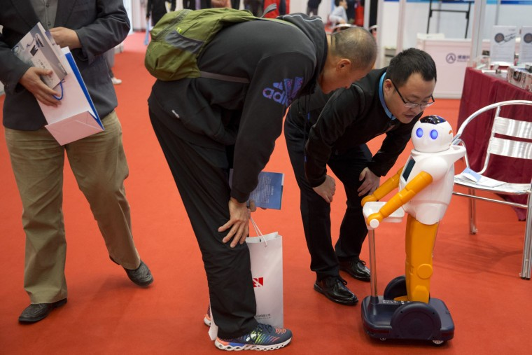 Visitors try to communicate with a robot during the World Robot Conference in Beijing, China, Friday, Oct. 21, 2016. The conference showcased China's burgeoning robot industry as the nation seeks to increase the use of robots in its manufacturing and service industries. (AP Photo/Ng Han Guan)