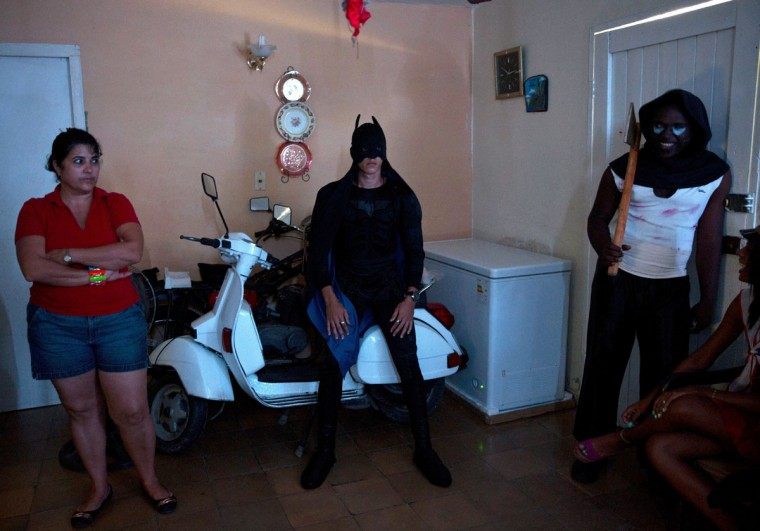 A young man dressed as Batman waits atop a Vespa scooter, stored in the living room of a home at the start of a Halloween party in Havana, Cuba, Friday, Oct. 28, 2016. Marta Perez, left, will be supervising the teen party, which her son is attending. (AP Photo/Ramon Espinosa)