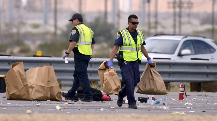 California Highway Patrol officers pick up items in bags after a tour bus crashed with a semi-truck on Interstate 10, west of the Indian Canyon Drive off-ramp, in Desert Hot Springs, near Palm Springs, Calif., Sunday, Oct. 23, 2016. The tour bus and the semi-truck crashed on the highway in Southern California early Sunday, killing at least a dozen of people and injuring at least 30 others, some critically, the California Highway Patrol said. (AP Photo/Rodrigo Pena)