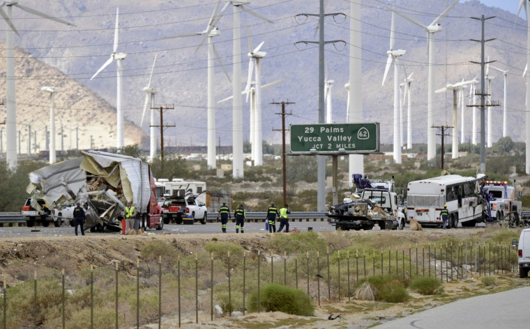 Tow truck drivers prepare to haul away a tour bus that crashed with a semi-truck on Interstate 10, west of the Indian Canyon Drive off-ramp, in Desert Hot Springs, near Palm Springs, Calif., Sunday, Oct. 23, 2016. The tour bus and the semi-truck crashed on the highway in Southern California early Sunday, killing at least a dozen of people and injuring at least 30 others, some critically, the California Highway Patrol said. (AP Photo/Rodrigo Pena)