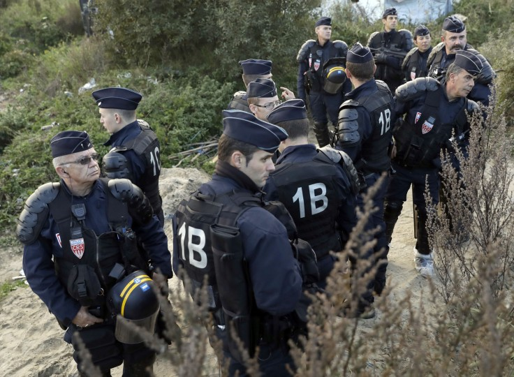 "Riot police take position while crews start to demolish shelters in the makeshift migrant camp known as ""the jungle"" near Calais, northern France, Tuesday, Oct. 25, 2016. Crews in hard hats and orange jumpsuits on Tuesday started dismantling a makeshift camp in France that has become a symbol of Europe's migrant crisis while thousands of people remained there waiting to be relocated. (AP Photo/Matt Dunham)"