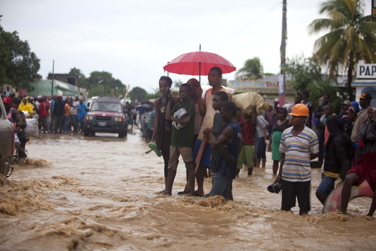 People stand in a street flooded by a nearby river overflowing from the heavy rains caused by Hurricane Matthew, in Leogane, Haiti, Wednesday, Oct. 5, 2016. Rescue workers in Haiti struggled to reach cutoff towns and learn the full extent of the death and destruction caused by Hurricane Matthew as the storm began battering the Bahamas on Wednesday and triggered large-scale evacuations along the U.S. East Coast. (AP Photo/Dieu Nalio Chery)