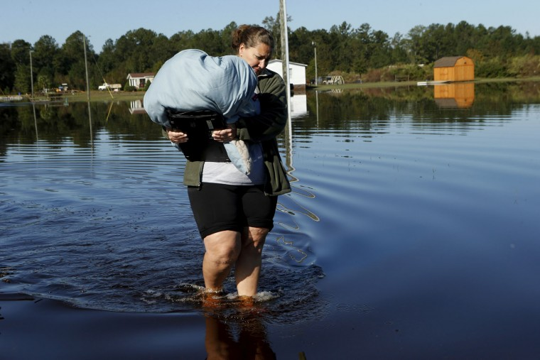 Janet Meier wades through the floodwaters associated with Hurricane Matthew surrounding her home as she makes her way back to her car after retrieving a warm blanket and her laptop on Thursday, Oct. 13, 2016, in Lumberton, N.C. About 1,200 Lumberton residents had to be evacuated by boat and plucked from their roofs by helicopters as the river crested. (AP Photo/Brian Blanco)