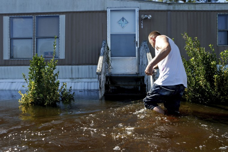 Elmer McDonald braces himself on the handrail to his front steps as makes his way through a strong current in his front yard while returning to his mobile home for the first time to inspect damage caused by floodwaters associated with Hurricane Matthew on Thursday, Oct. 13, 2016, in Lumberton, N.C. About 1,200 Lumberton residents had to be evacuated by boat and plucked from their roofs by helicopters as the river crested; McDonald was one of thousands who evacuated. (AP Photo/Brian Blanco)