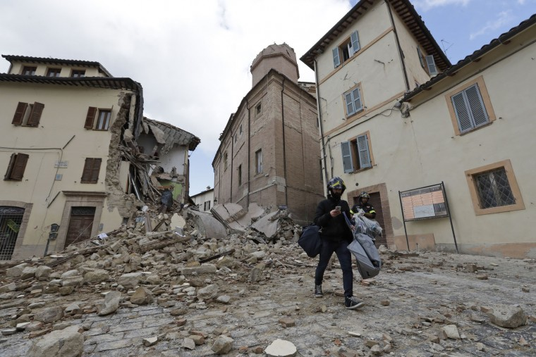A resident carrying his belongings passes in front of the collapsed bell tower of the Santa Maria in Via church in the town of Camerino, in central Italy, Thursday, Oct 27, 2016, after a 5.9 earthquake destroyed part of the town. Authorities began early Thursday to assess the damage caused by a pair of strong quakes in the same region of central Italy hit by the deadly August temblor, as local officials appealed for temporary housing adequate for the cold mountain temperatures with winter's approach. (AP Photo/Alessandra Tarantino)