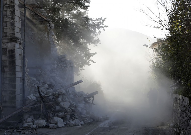 People walk among the dust after a wall fell in the small town of Visso in central Italy, Thursday, Oct 27, 2016, after a 5.9 earthquake destroyed part of the town. Authorities began early Thursday to assess the damage caused by a pair of strong quakes in the same region of central Italy hit by the deadly August temblor, as local officials appealed for temporary housing adequate for the cold mountain temperatures with winter's approach. (AP Photo/Alessandra Tarantino)