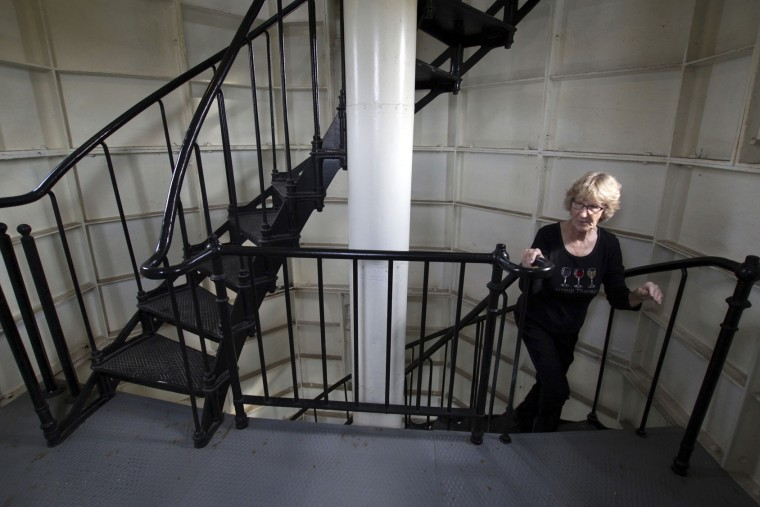 In this photo taken Sunday, Sept. 25, 2016, Marian Gladieux, of Oregon, Ohio, walks up the tower of the North Point Lighthouse in Milwaukee. A group of volunteers spent about a decade acquiring and renovating the living quarters and tower, opening it to the public in 2007. (AP Photo/Carrie Antlfinger)
