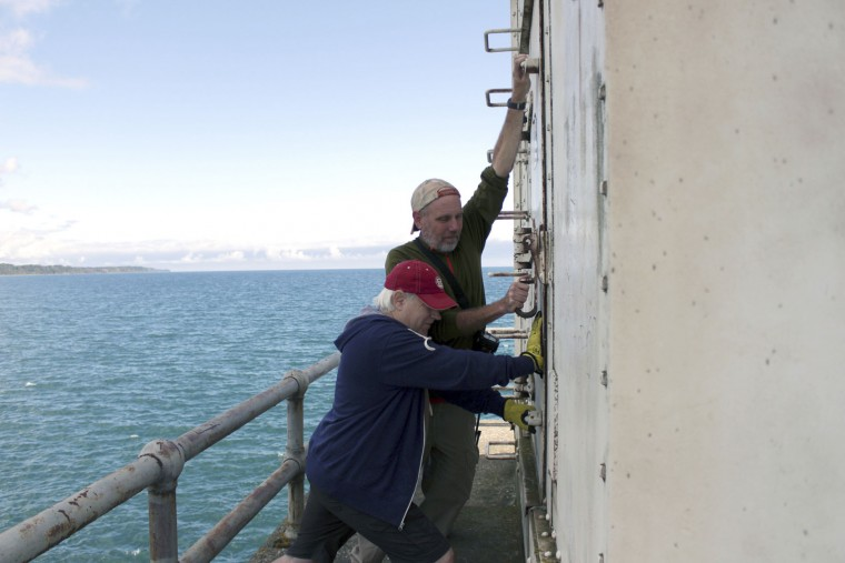 In this photo taken Oct. 3, 2016, Ross Kroeger and John Reichert, left, close the door to the light head tower on the Port Washington, Wis., breakwater. The city is in the process of acquiring it, with plans to raise and spend $1.5 million to restore. (AP Photo/Carrie Antlfinger)