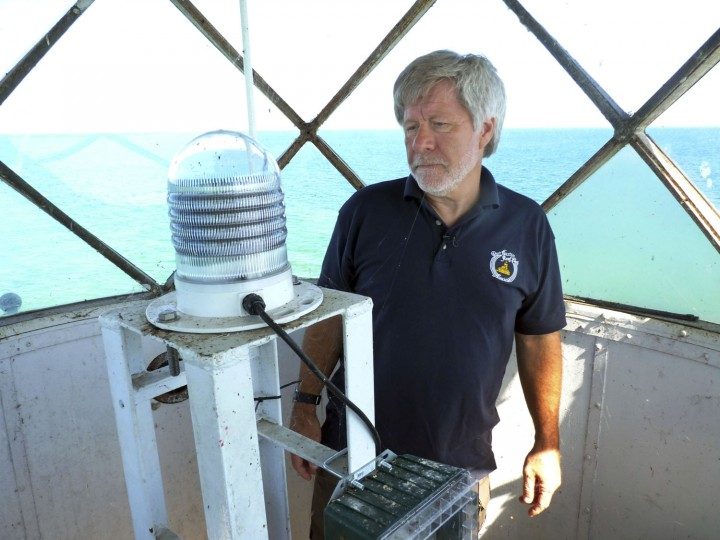 In this photo taken Monday, Sept. 12, 2016, Marv Kuziel of the Port Austin Reef Light Association shows the light that guides vessels from the top of the Port Austin Reef Lighthouse more than two miles off the Michigan shore in Lake Huron's Saginaw Bay. Members of the nonprofit association have worked for decades to restore the structure, which was last inhabited by light keepers in 1952. (AP Photo/Roger Schneider)