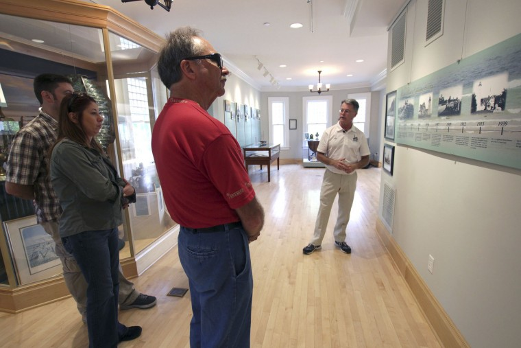 In this photo taken Sunday, Sept. 25, 2016, Michael Connor, right, gives tours at the North Point Lighthouse in Milwaukee. A group of volunteers spent about a decade acquiring and renovating the living quarters and tower, opening it to the public in 2007. (AP Photo/Carrie Antlfinger)
