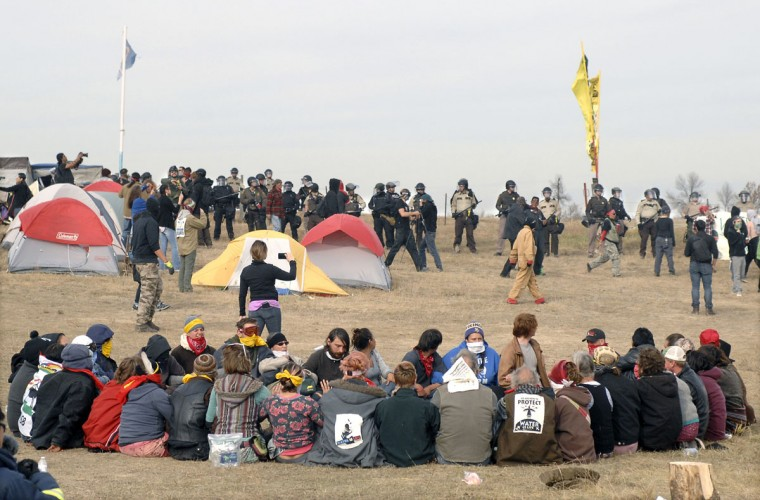 Dakota Access Pipeline protesters sit in a prayer circle at the Front Line Camp as a line of law enforcement officers make their way across the camp to remove the protesters and relocate to the overflow camp a few miles to the south on Highway 1806 in Morton County, N.D., Thursday, Oct. 27, 2016. (Mike McCleary/The Bismarck Tribune via AP)
